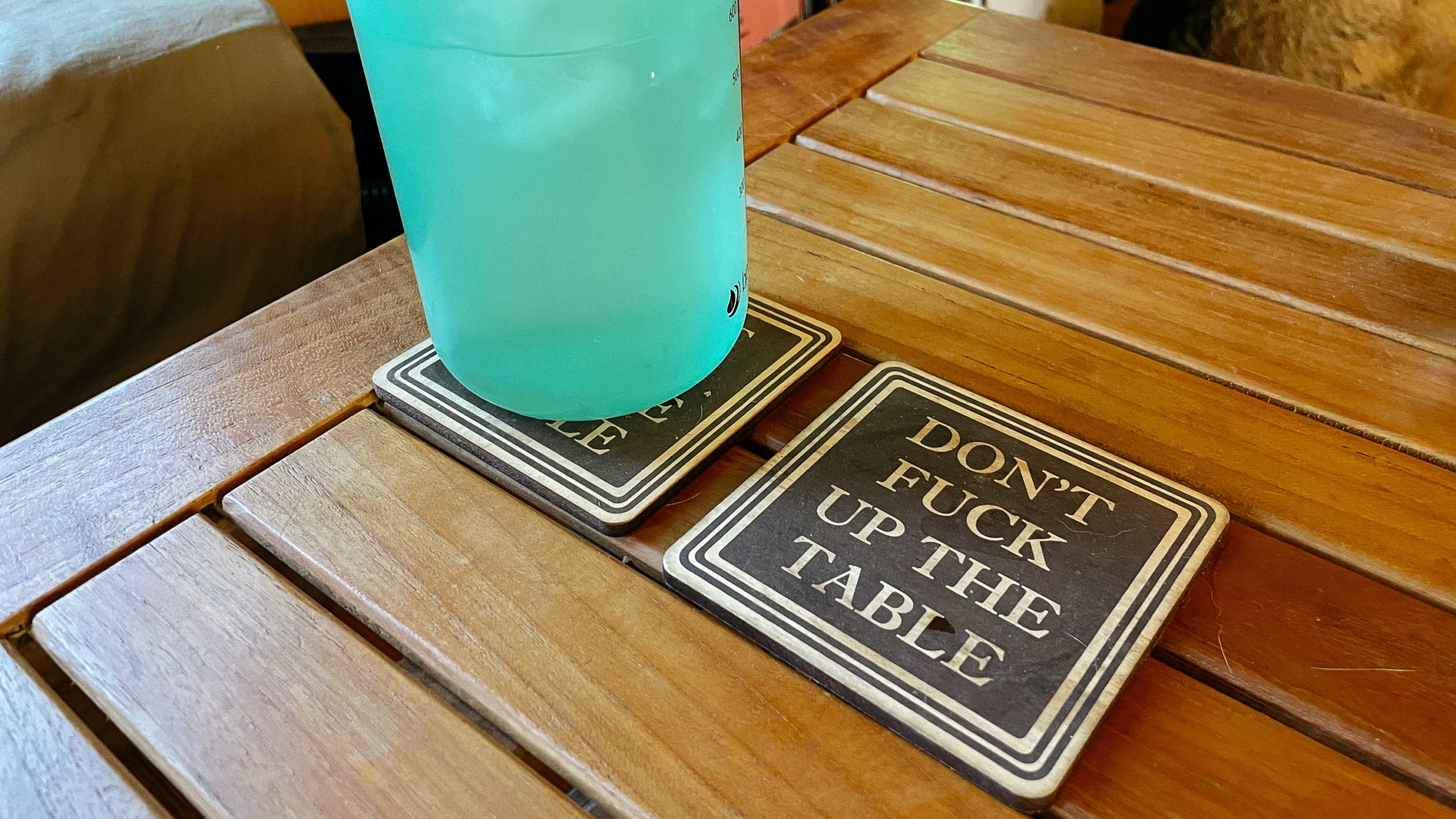 """A funny coaster that reads """"Don't fuck up the coffee table"""""""