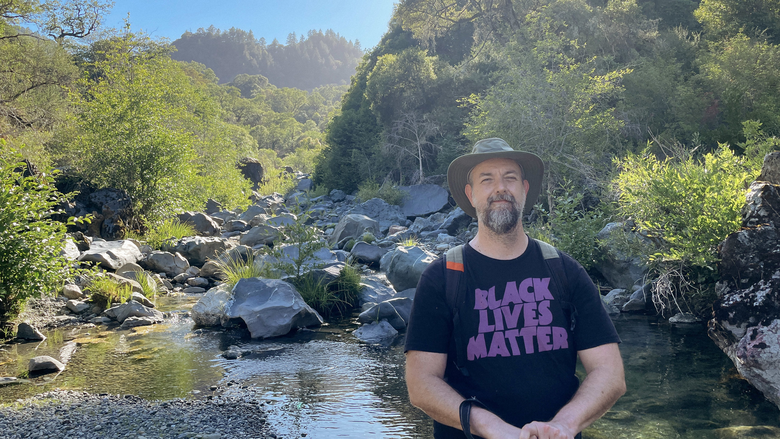 A man in a Black Lives Matter shirt with a hat in a rocky creek bed