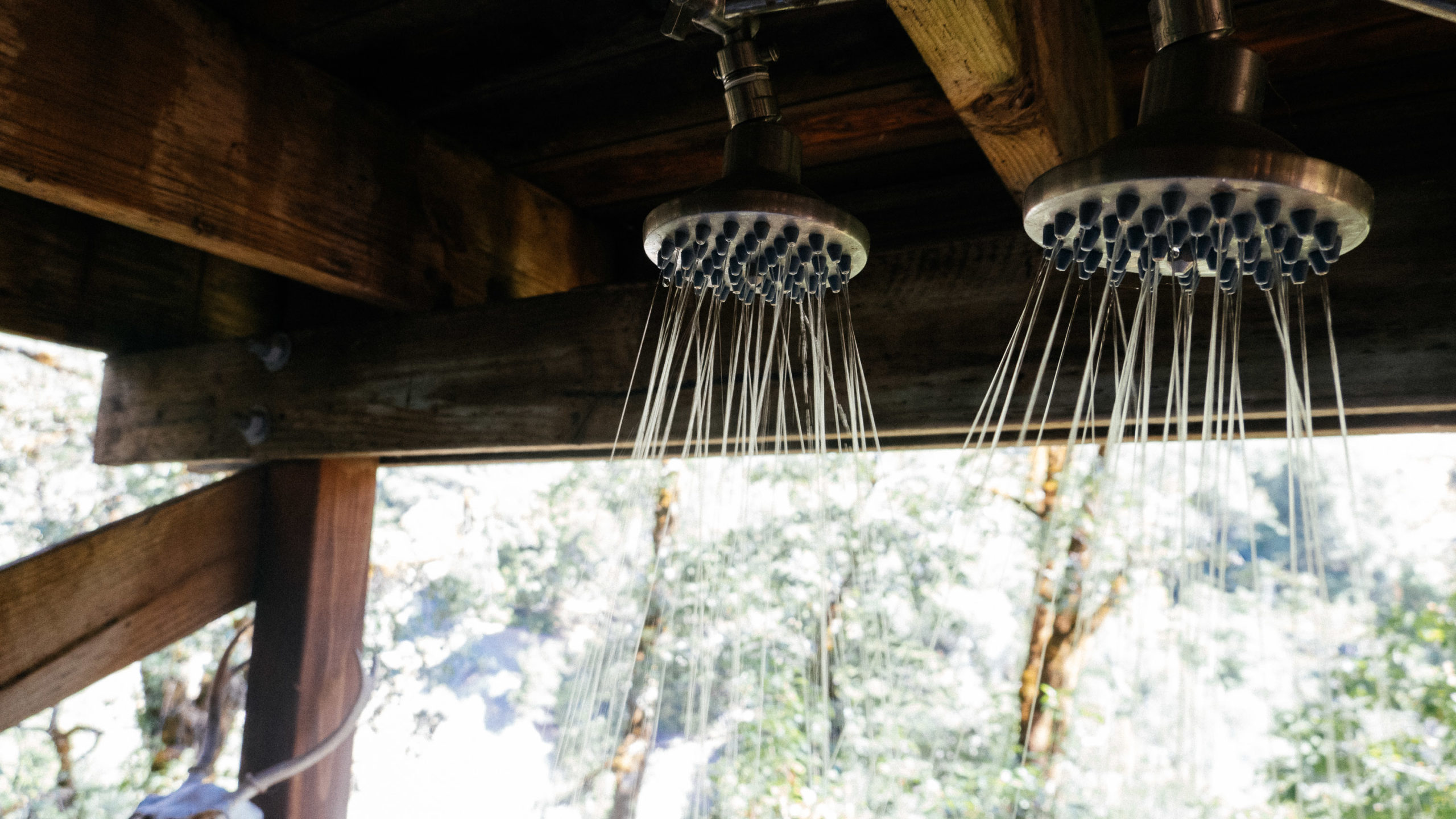 Double shower nozzles spray water in an outdoor shower
