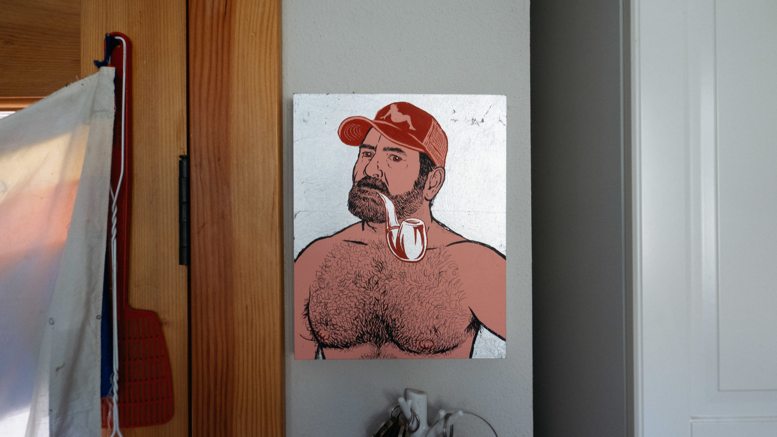 A portrait of shirtless man with a pipe and ballcap