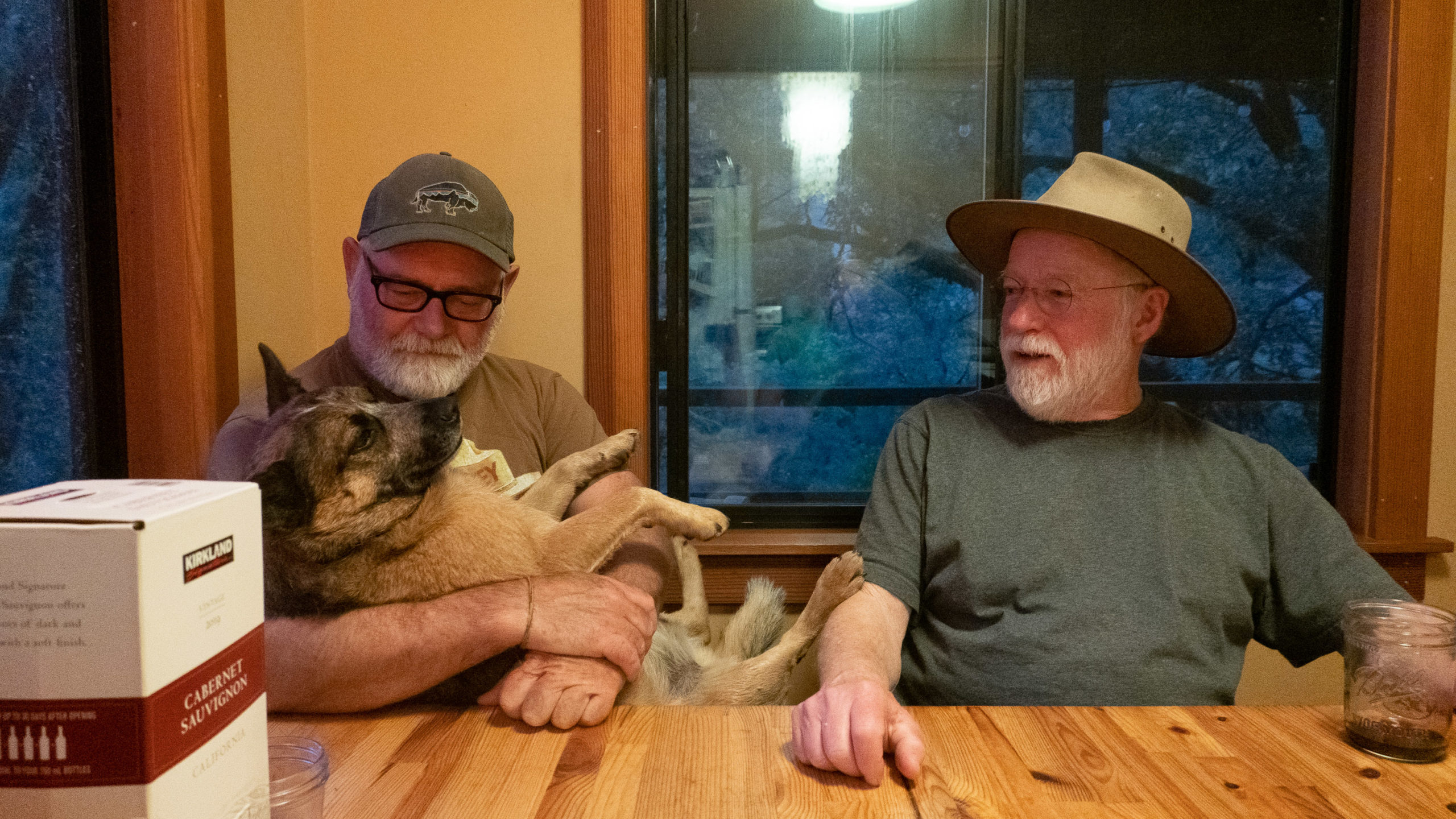 A man holds a dog while another man looks toward them