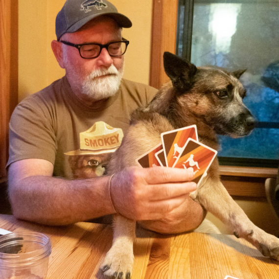 A man holds a dog while holding a set of game cards