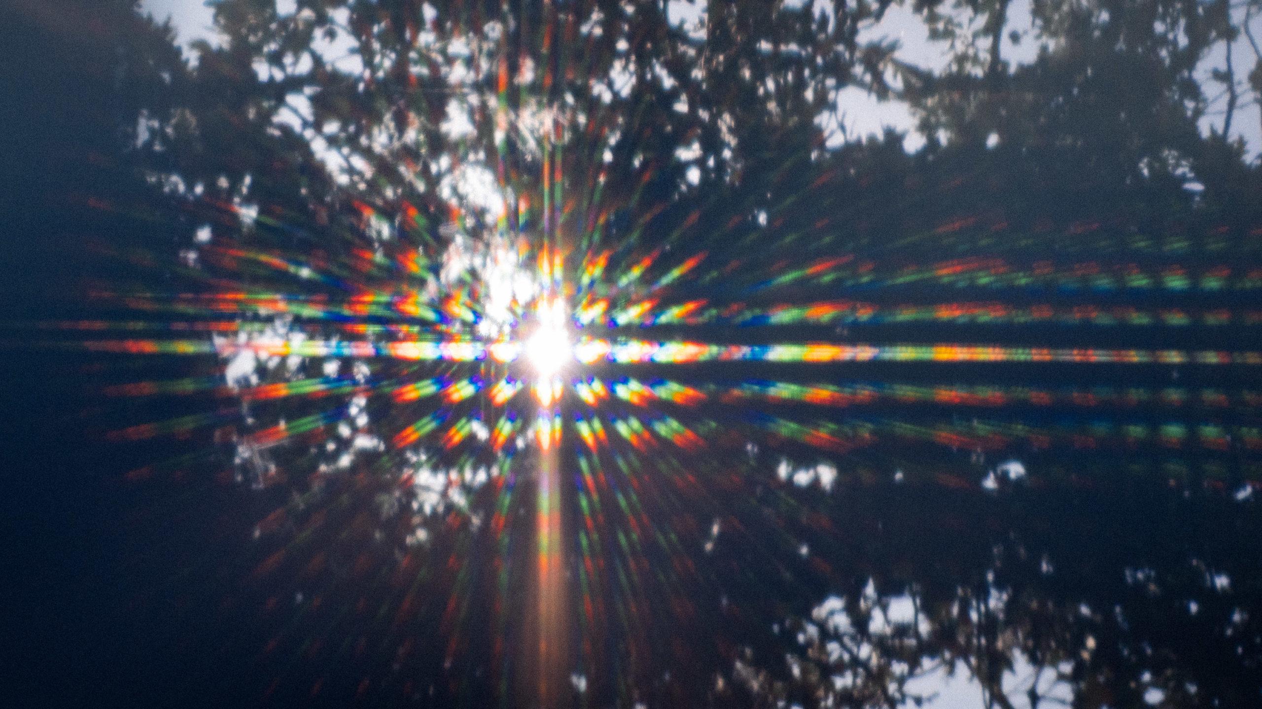refracted light creates a sunburst of rainbows on a laptop screen