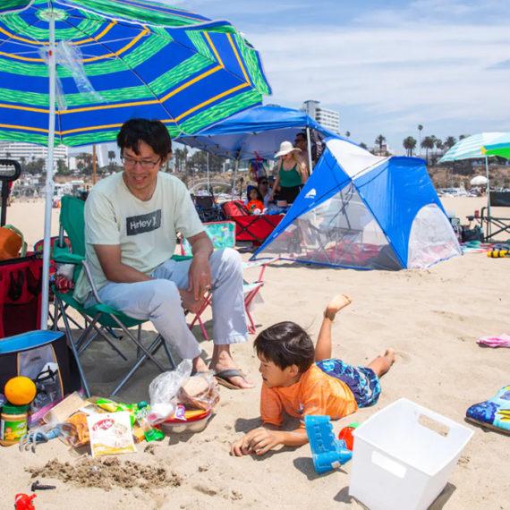 A family on a beach under a large umbrella