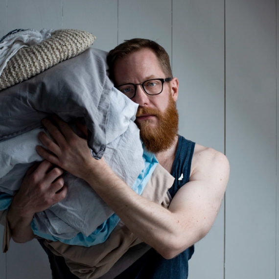 A bearded man with glasse holds a bundle of sheets and towels and fabric items