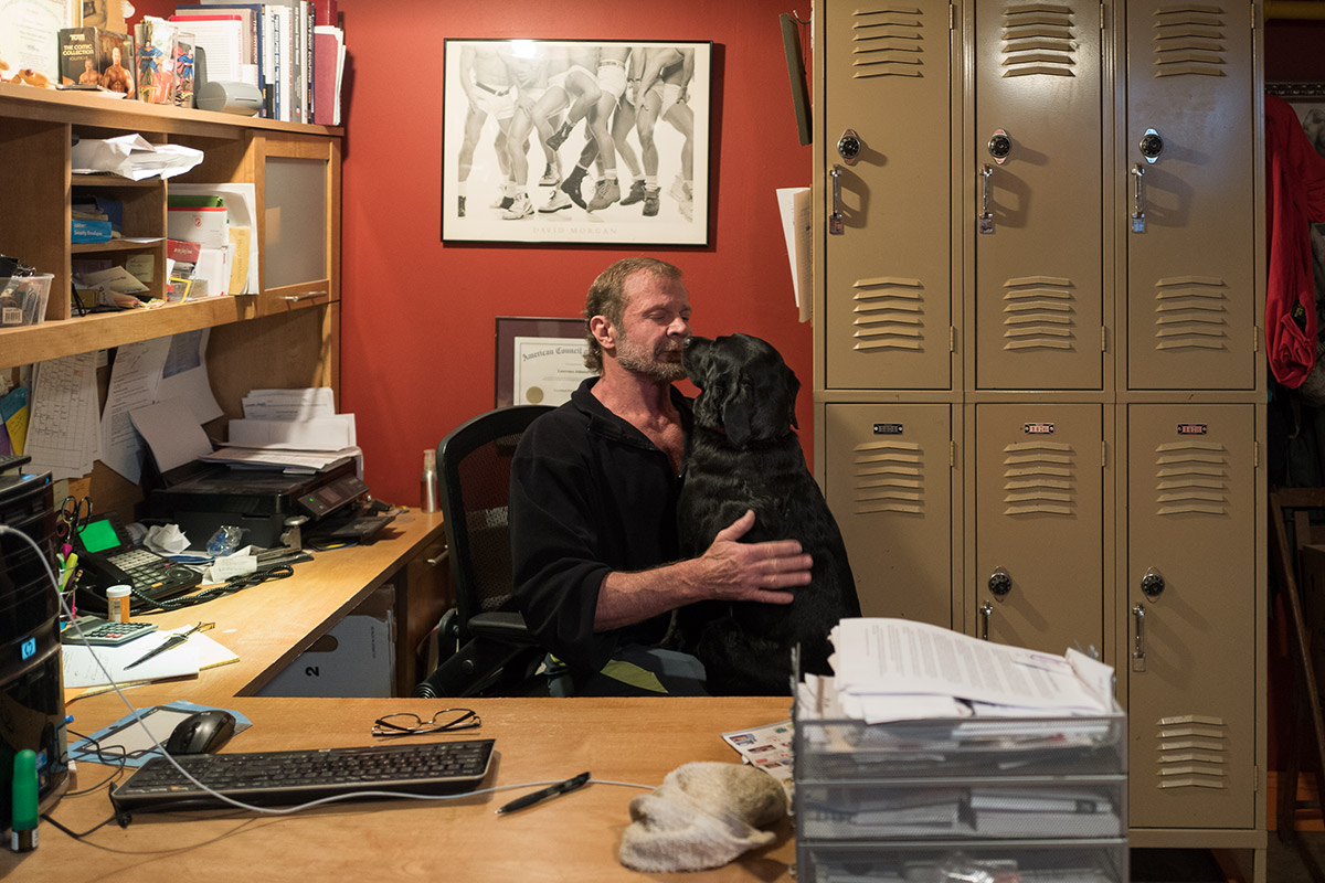 A man sits at a desk with a dog in his lap