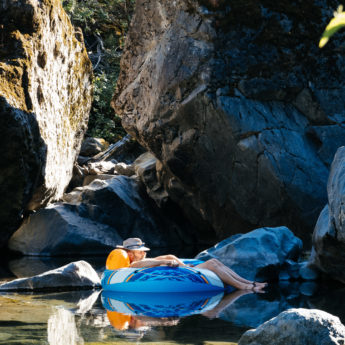Joe basks in the sun while floating on the creek in an inner tube