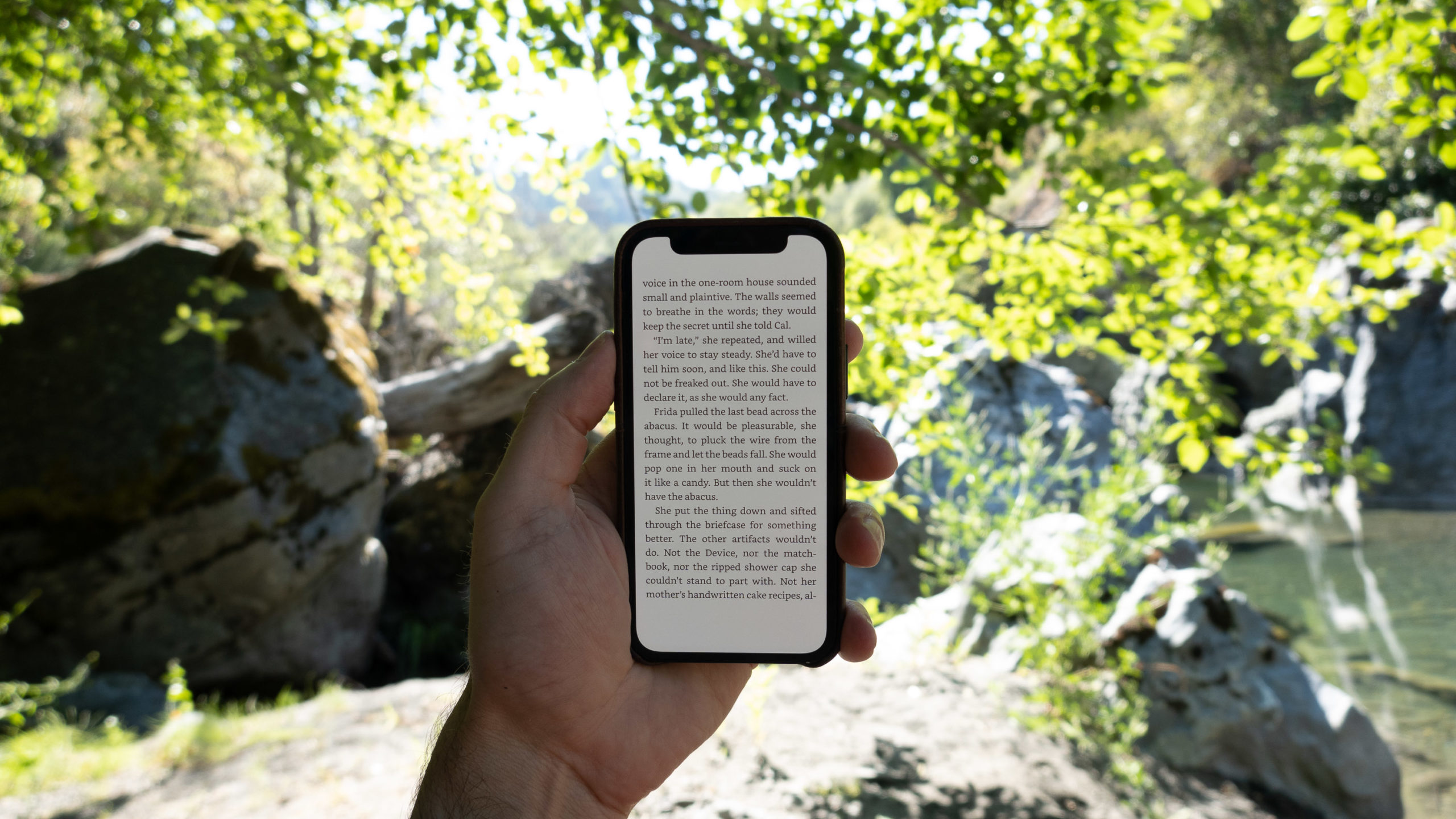 Reading a book under the trees on a mobile phone