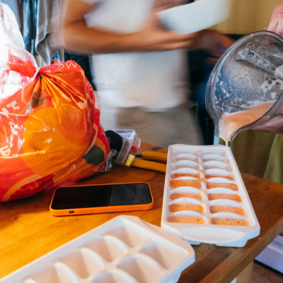 Pouring grapefruit juice into ice cube trays