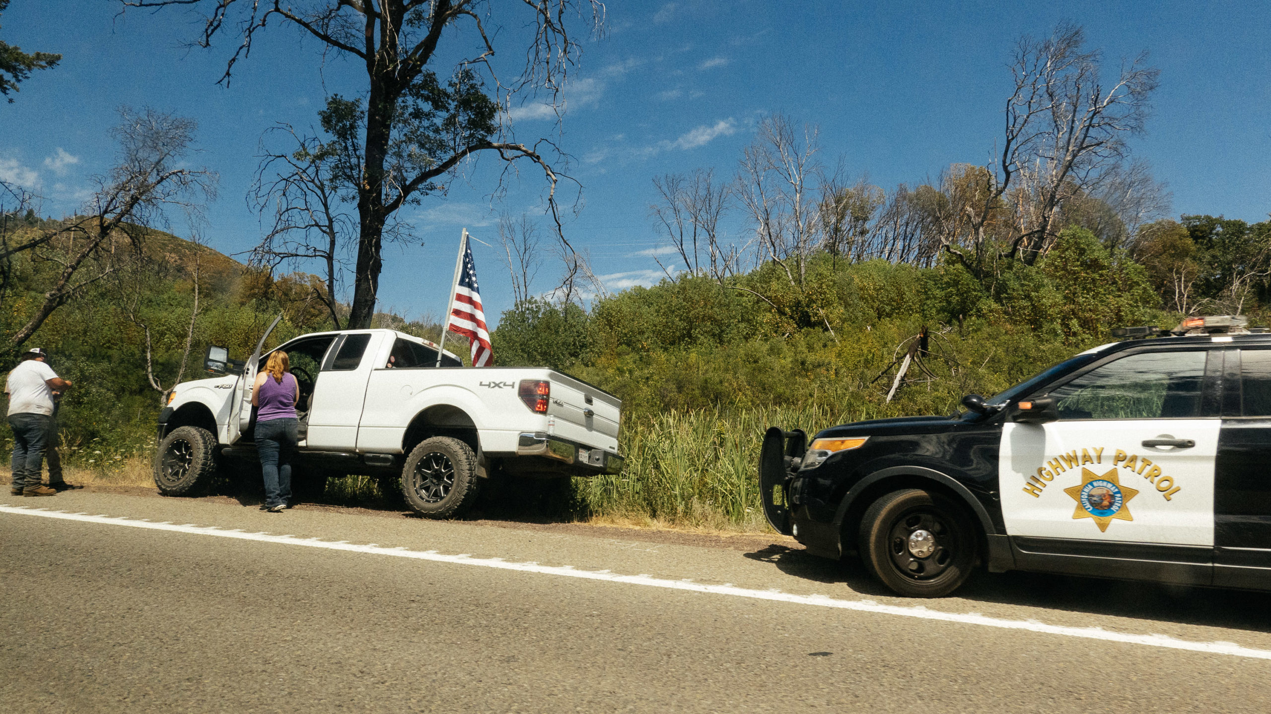 A white Ford F-150 with a large American flag off to the side of the road with a police car behind it