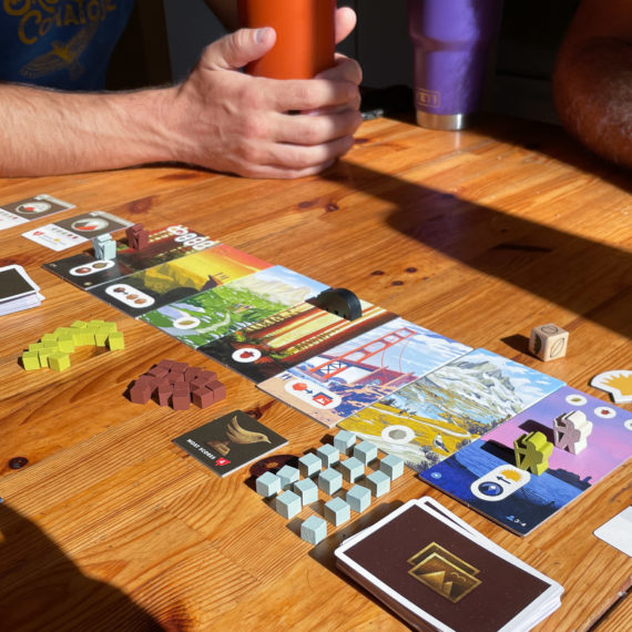 A board game set up on a wooden table in the late afternoon sun