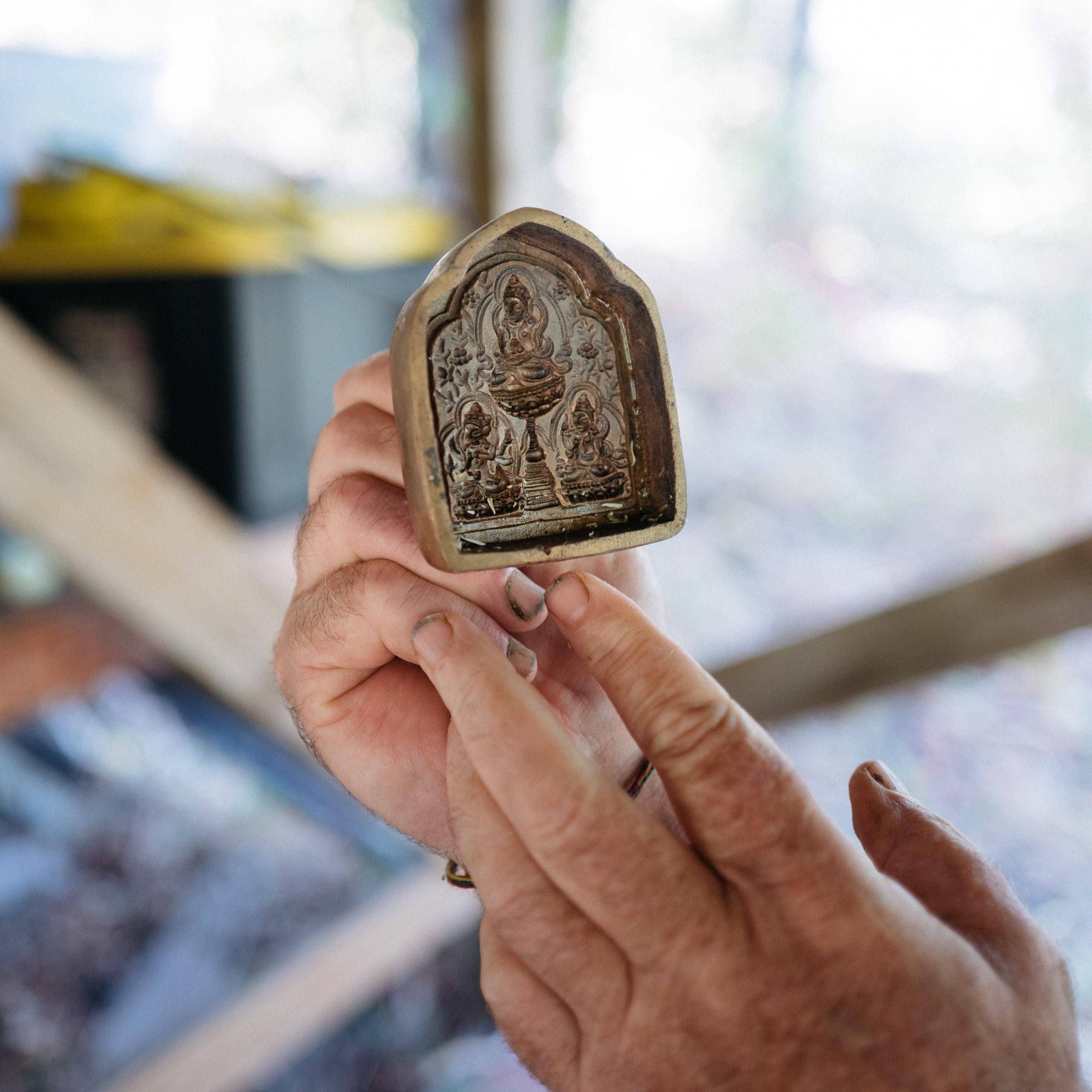 Hands holding a metal tsa-tsa form of Tara