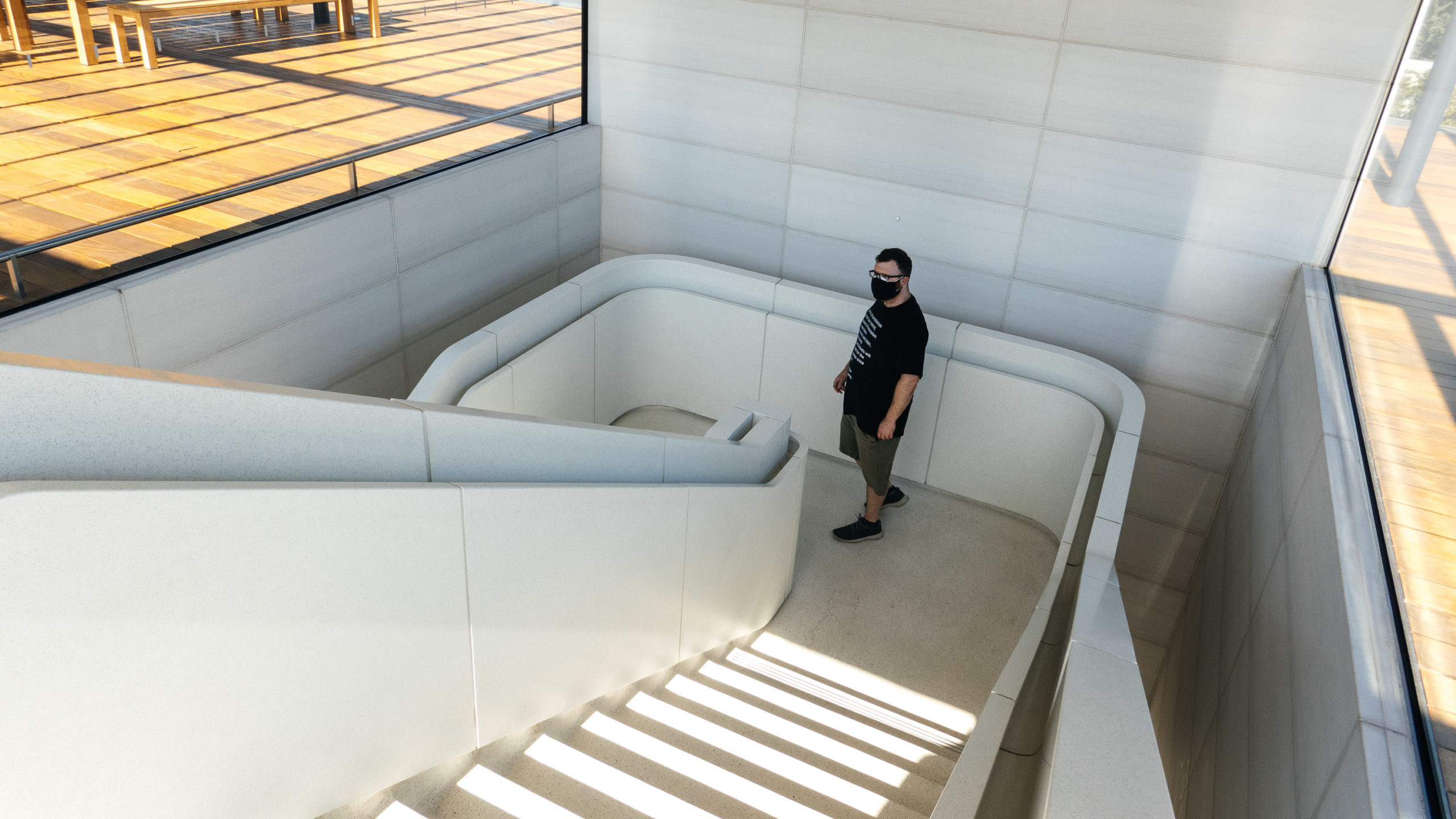 A man in a mask walks down a modern set of stairs.