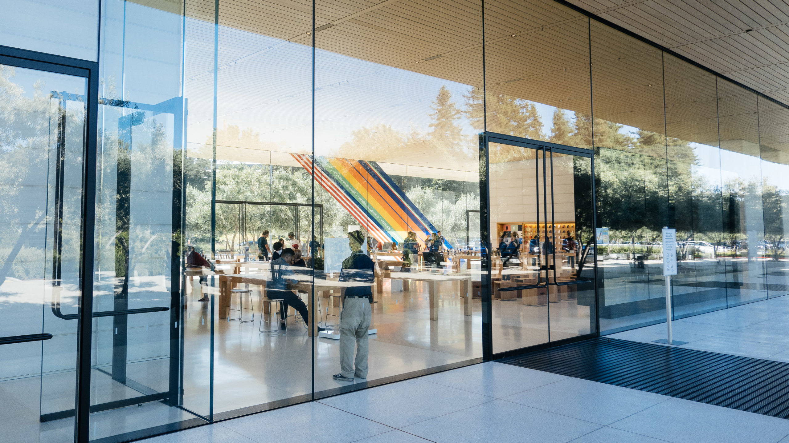 Viewing through large panes of glass, the interior of an Apple Store is revealed