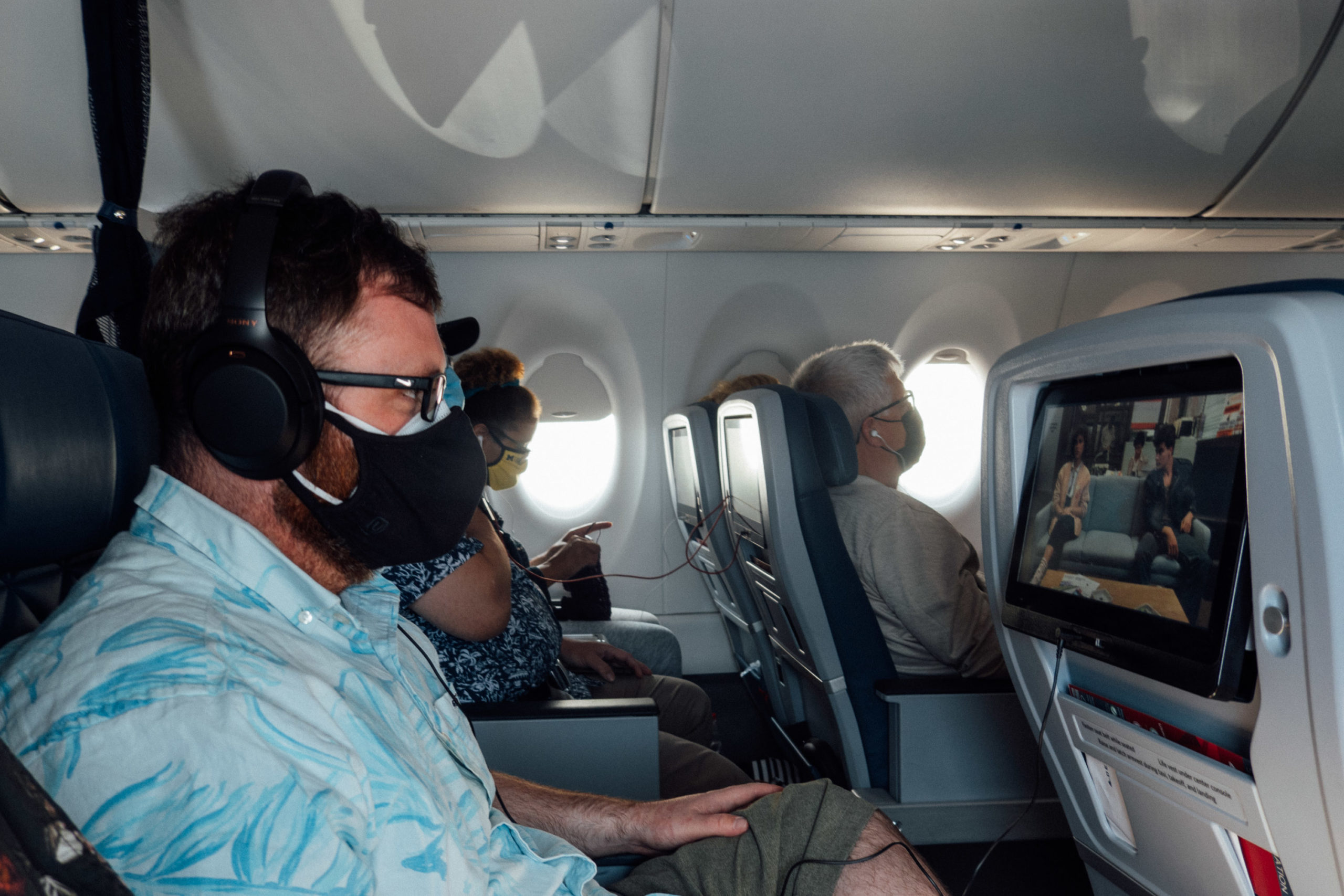 A bearded man with double facemasks on an airplane watches Ferris Bueller's Day Off on a seatback video screen