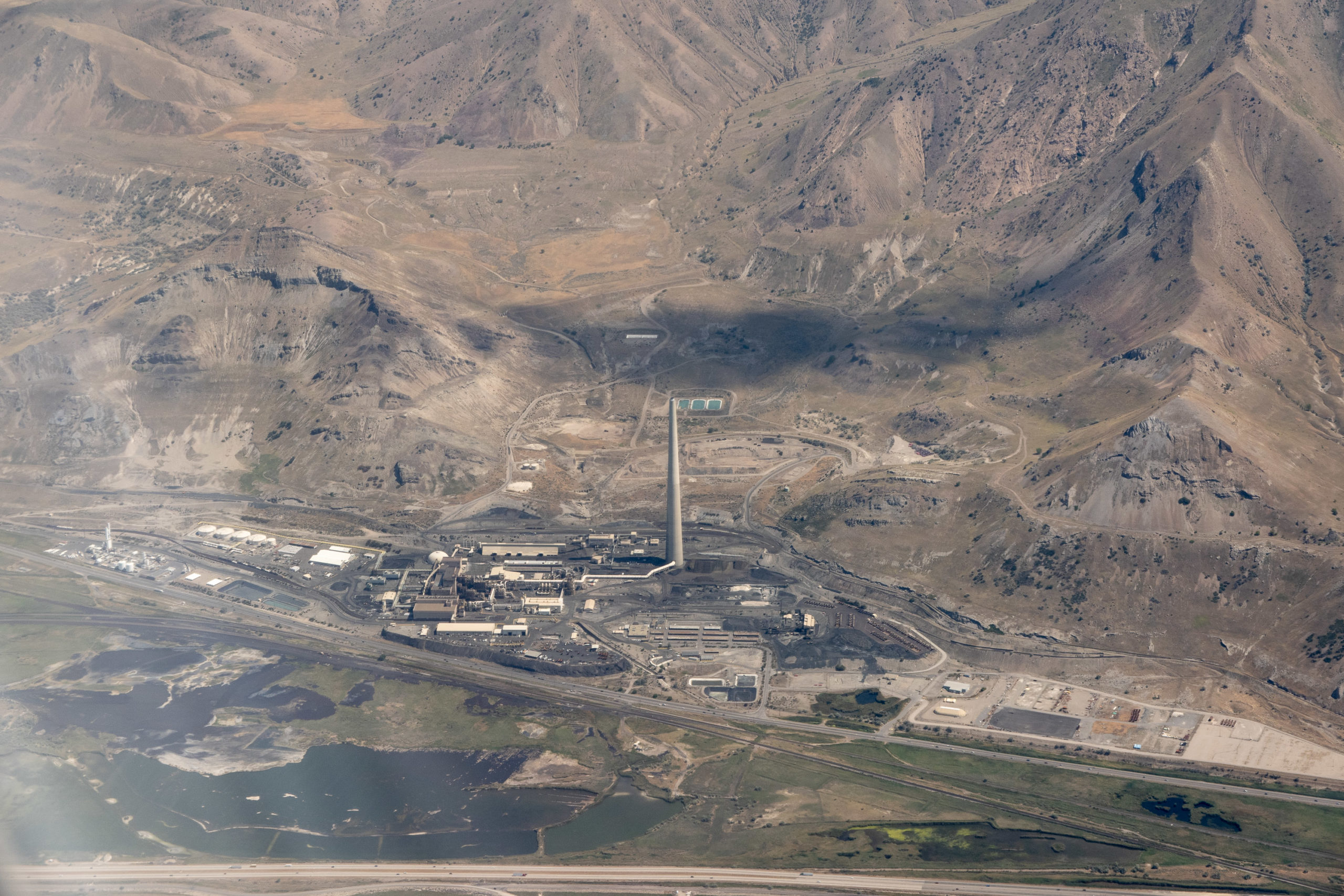 A very tall smokestack at the base of the Oquirrh Mountains