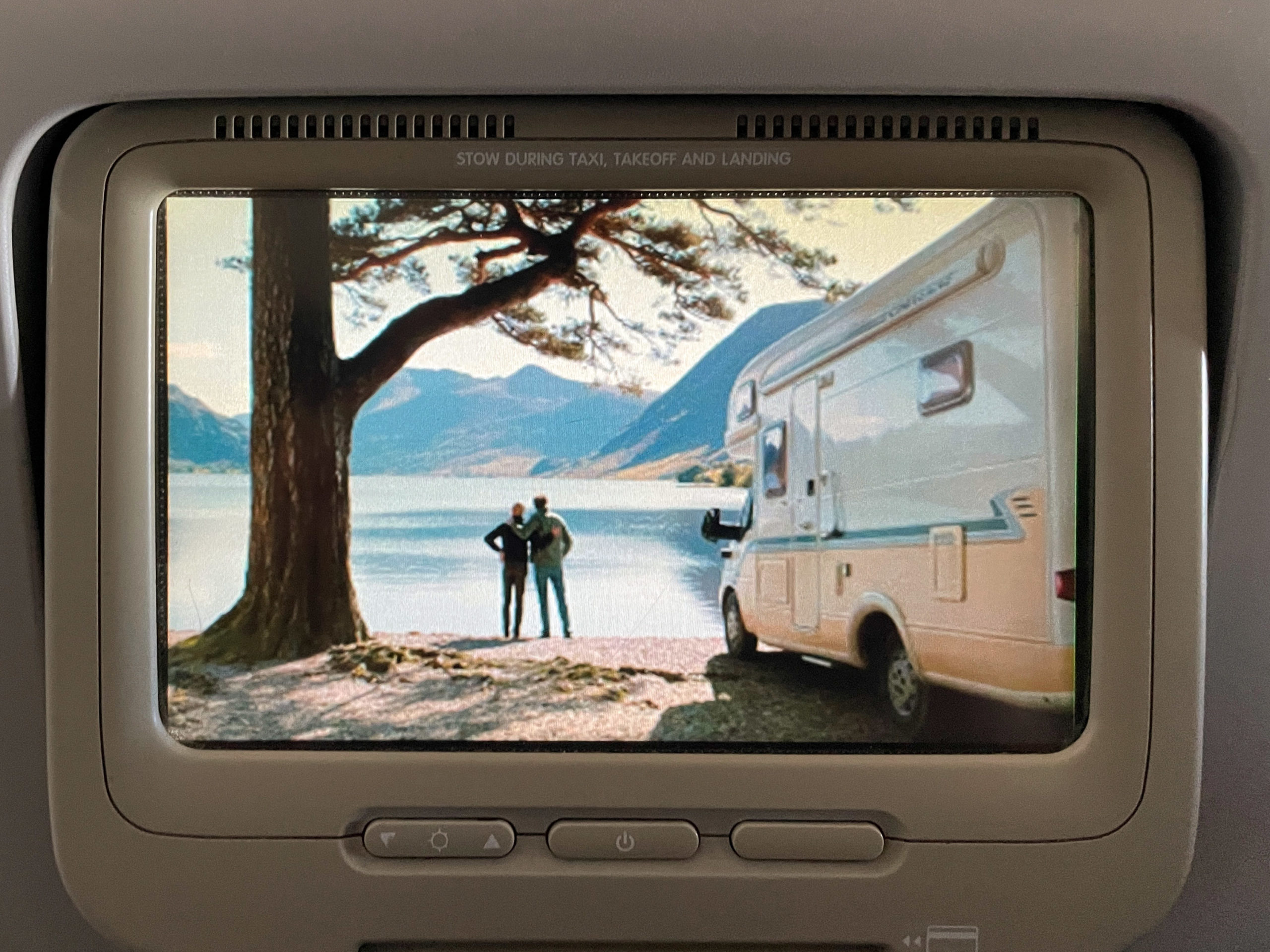Photograph of a seatback video screen on a flight. The scene is of two men with their arms around another at the edge of a lake with an RV in the foreground