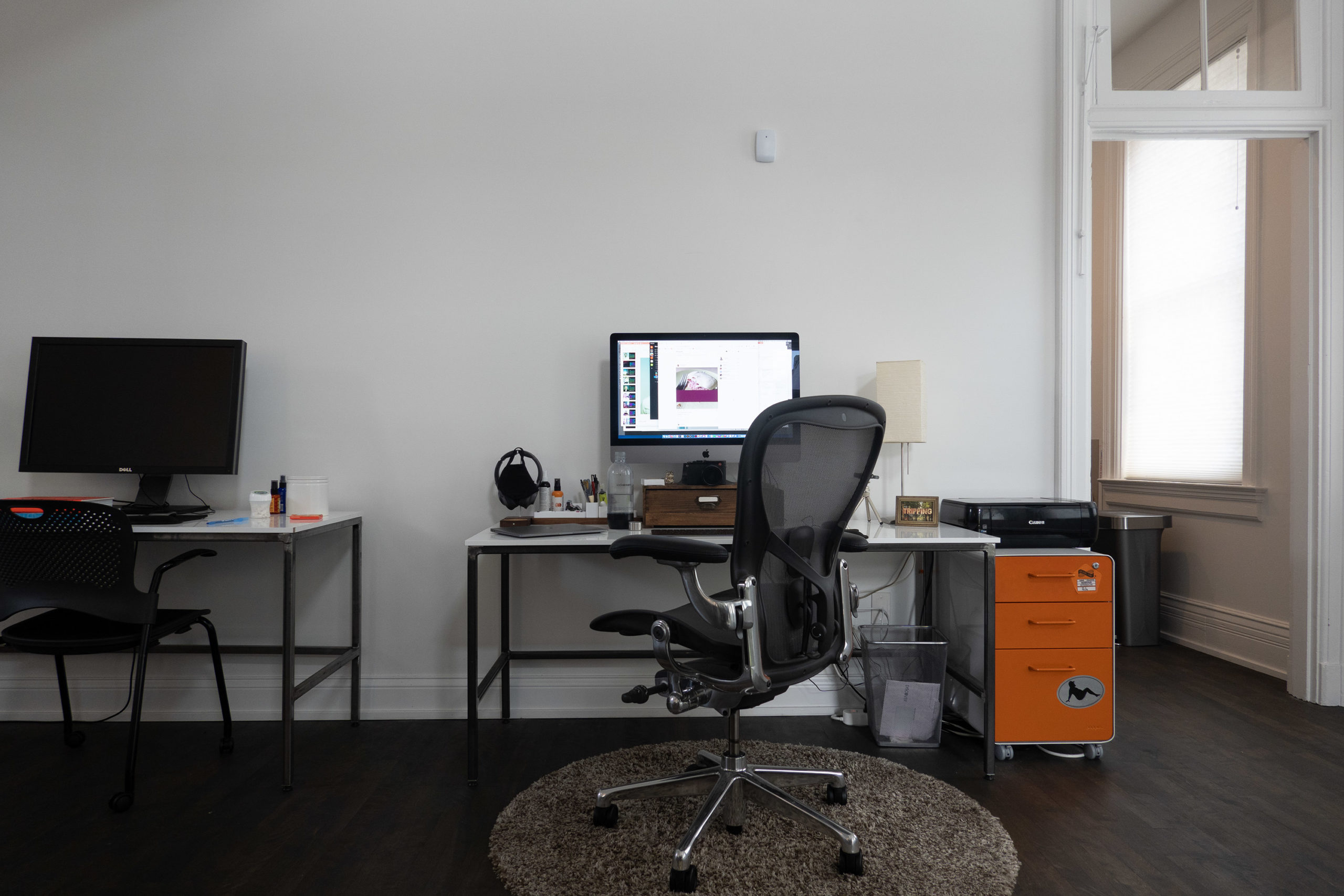 A desk with a computer and an orange filing cabinet off to the right