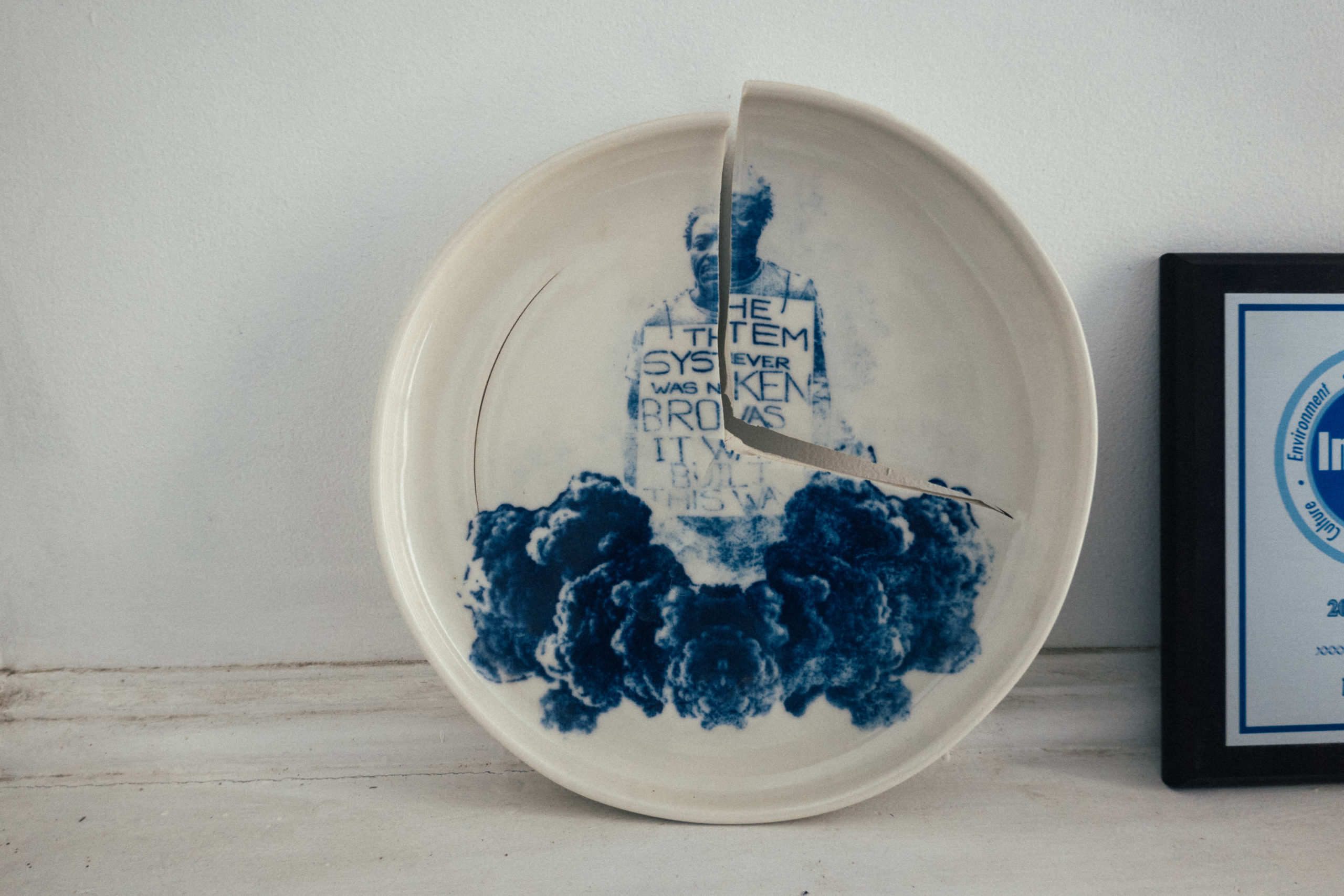 A broken plate with a screenprinted design in blue ink