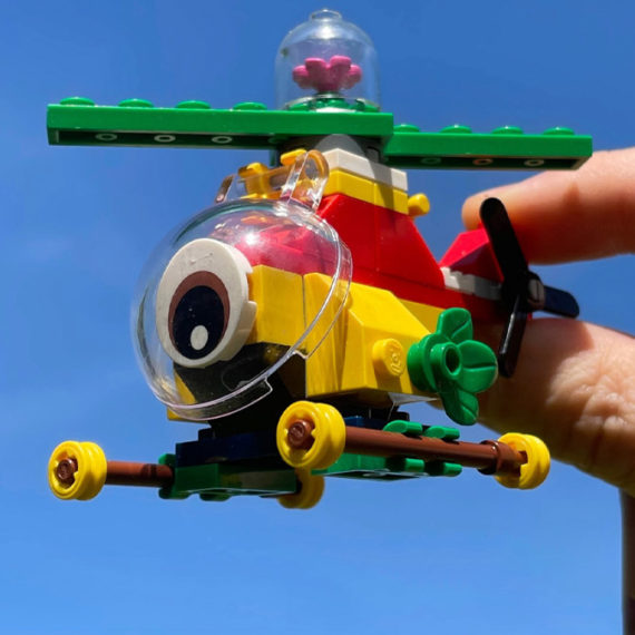 A colorful abstract Lego helicopter held by a hand