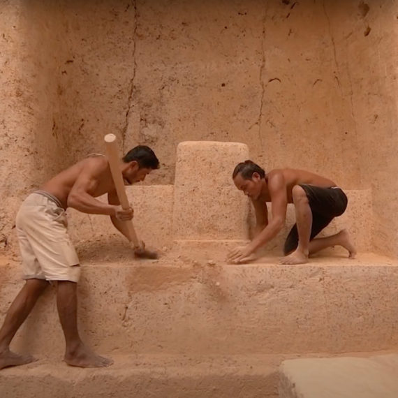 Two men work the earth in architectural ways