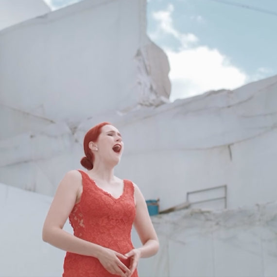 A woman in a red dress sings surrounded by a rock quarry