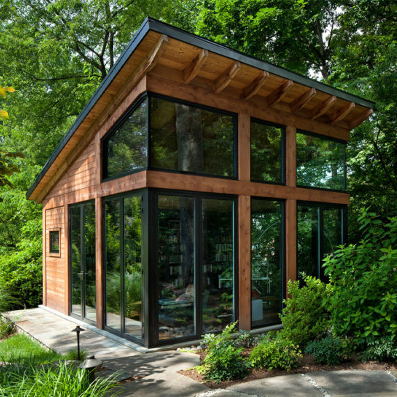 A modern small studio building set in the woods