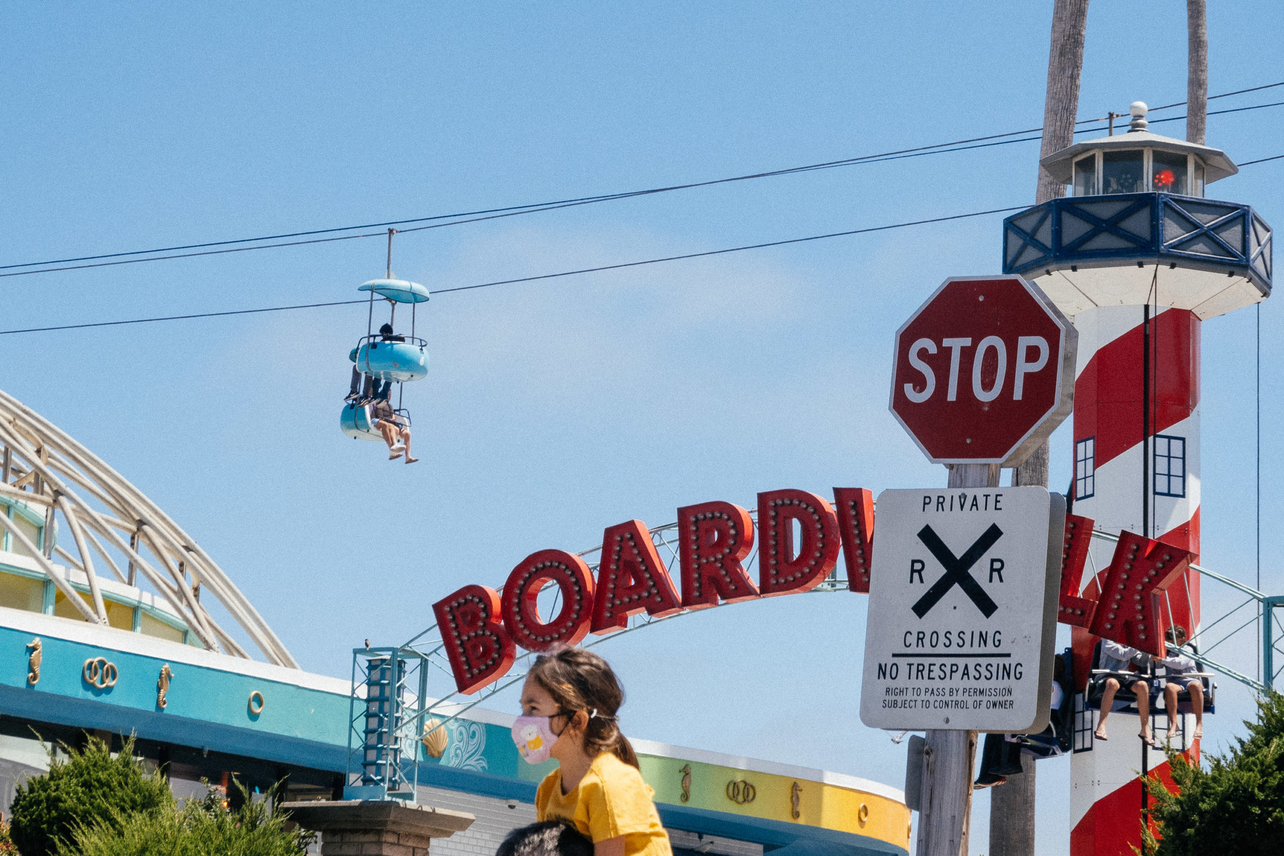 A teal sky lift goes across the sky along a coastal boardwalk amusement park