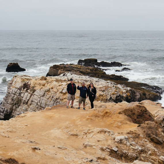 Three friends pose from a distance on a rocky outcropping at a coast