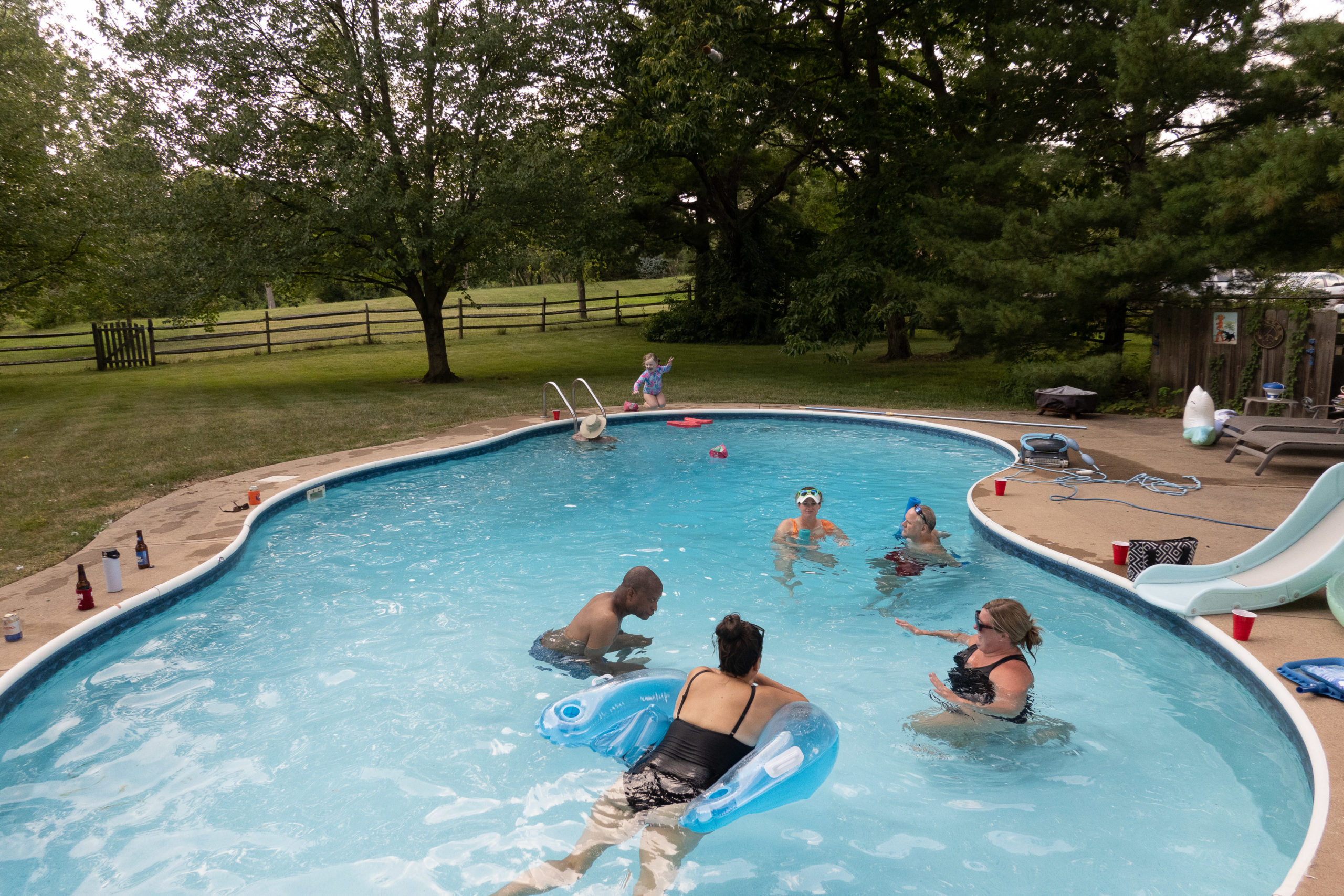 A group of folks hang out in a pool while a young girl jumps into it in the background
