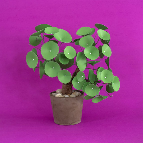 A handmade plant made with paper on a magenta backdrop