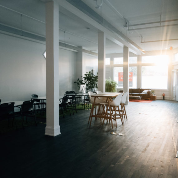 The sun beams through the windows of a large open workspace