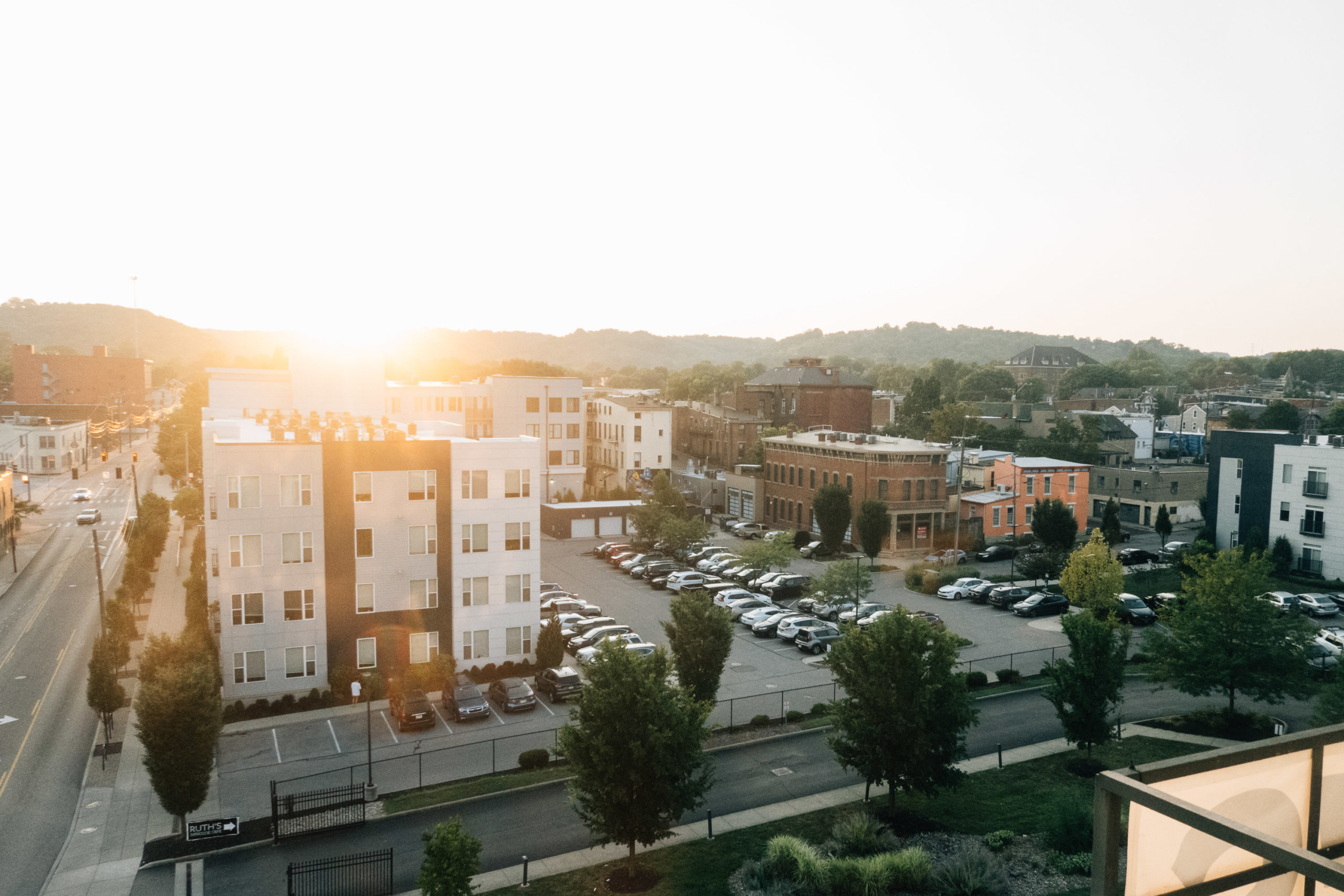 The sun sets over a modern apartment complex with questionable architecture and an old neighborhood with character