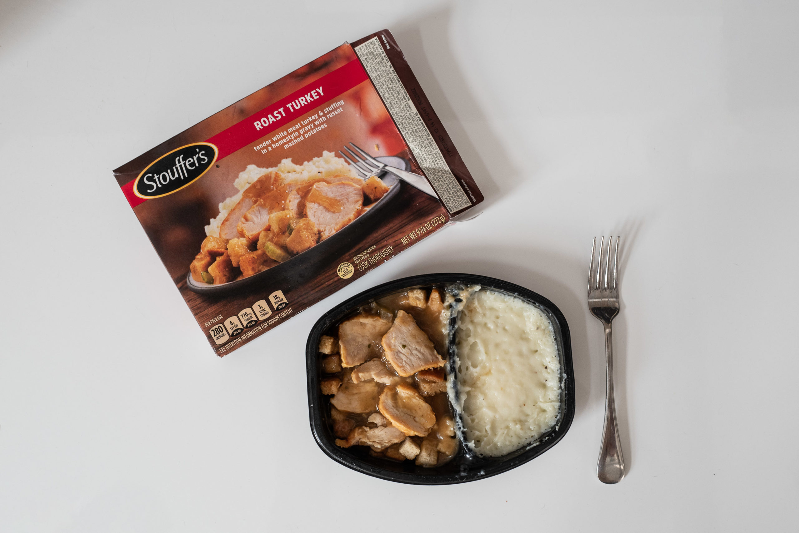 A cooked frozen meal of turkey and mashed potatoes next to the box it came in.