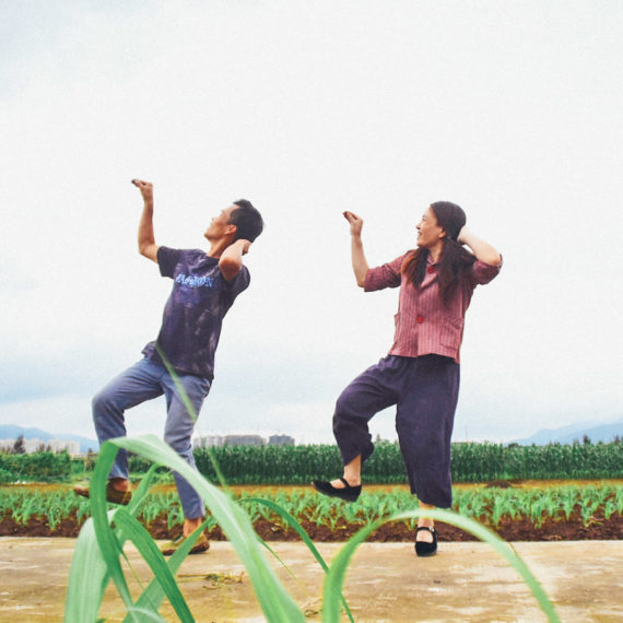 A man and woman dance alongside a field in China