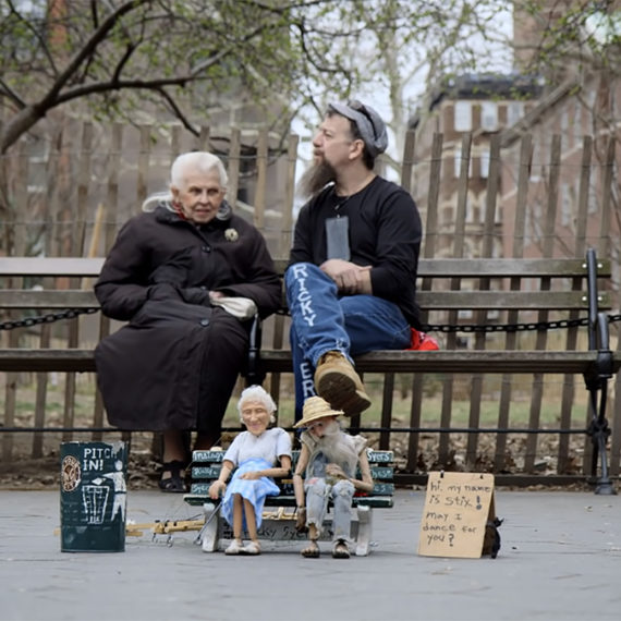 A woman and man sit on a park bench in the background while thie doppleganger marionettes sit in front